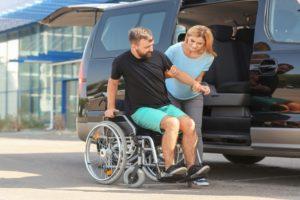 Woman Helping Patient in Wheelchair Get into Van