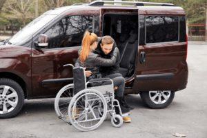 Man helping woman in wheelchair into van