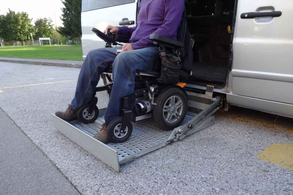 Person on wheelchair lift for van