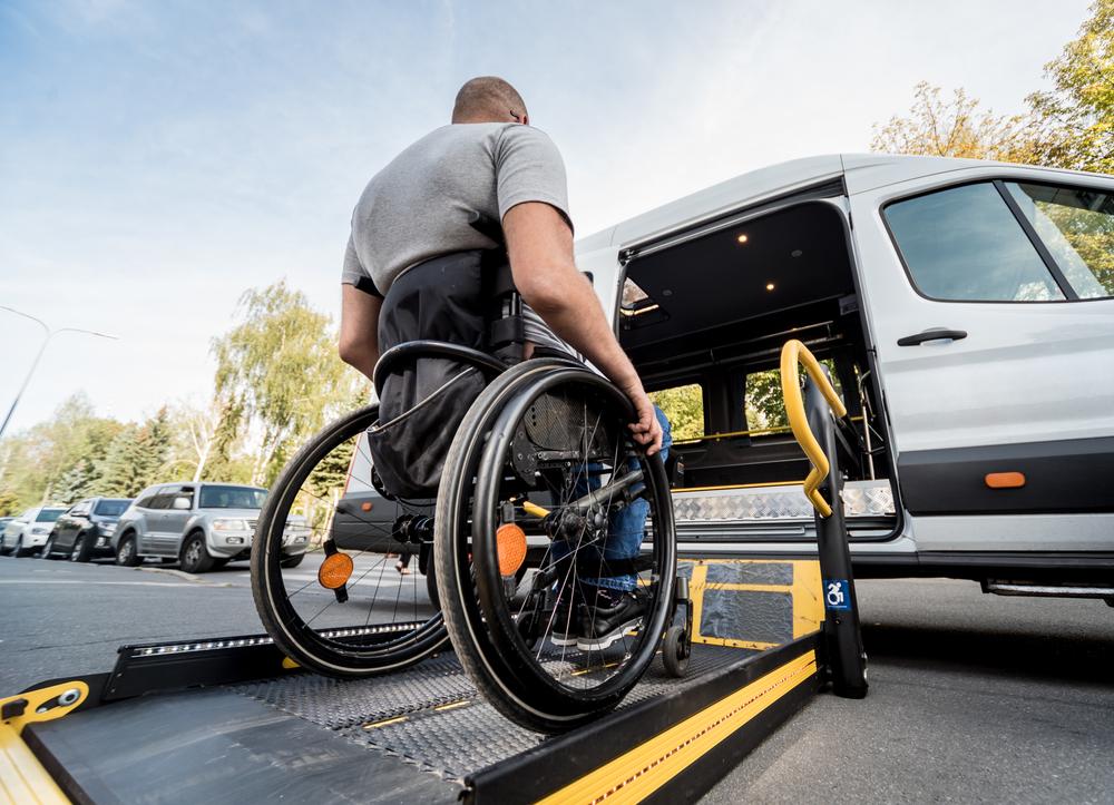 A man in a wheelchair on a lift for an NEMT van